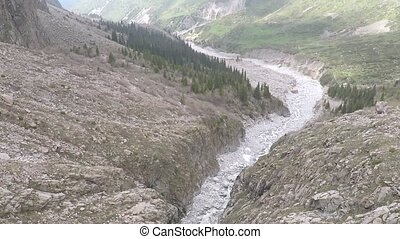 Aerial camera follows mountain stream on white rocks. High altitude shot