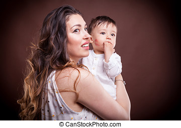 Kissed baby son by her mother looking away from the camera...