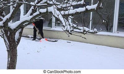 House keeper man clean snow from footpath near home in...