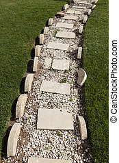 Beautiful path of white stones on a lawn of green grass. -...