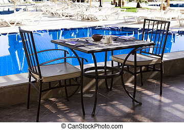 Table and chairs by the pool, Breakfast in Ibiza The morning...