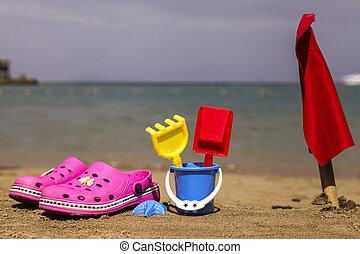 Pink beach shoes and blue sand toys on sandy beach.Beach...