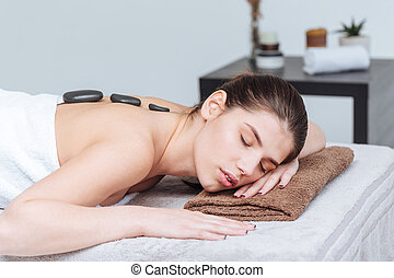 Woman relaxing and receiving hot stone massage in spa salon...