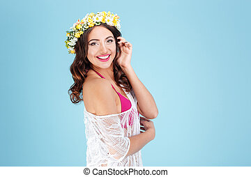 Happy cheerful lady wearing flower diadem over blue...