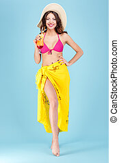 Young sexy brunette with a coctail wearing beach hat - Young...