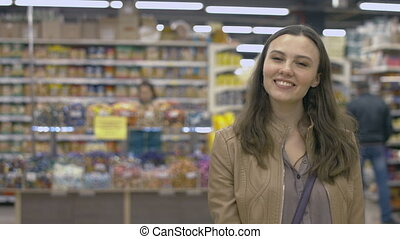 Happy girl standing in the supermarket and smiling