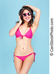 Portrait of a pretty smiling woman in sunglasses and bikini...