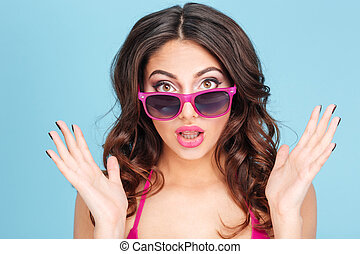 Close-up portrait of surprised girl in sunglasses over blue...