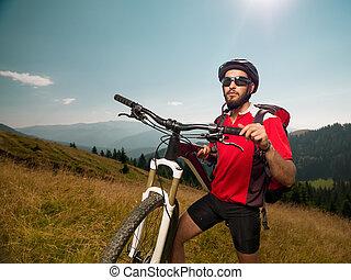 mountain biker on a meadow, along bike, looking forward,...