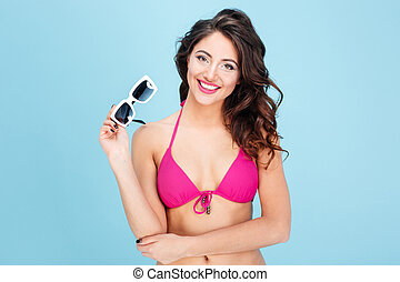 Close-up portrait of an attractive girl holding sunglasses -...