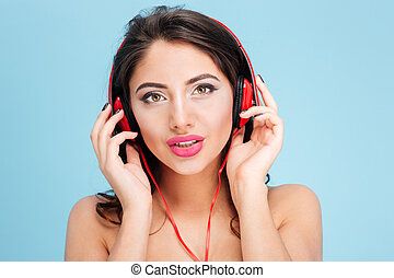 Pretty young woman wearing headphones over blue background -...