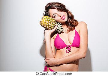 Pretty beautiful beach girl in bikini holding pineapple -...