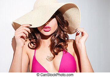 Close-up portrait of a young woman in beach hat - Close-up...