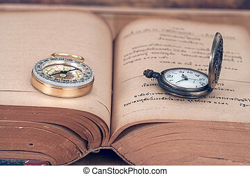 Vintage Compass and pocket watch on old books.