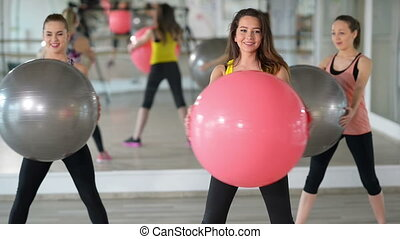 Aerobics at Gym - People exercising with fitness ball at gym