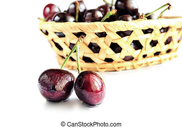 Two berries of sweet cherry and basket on a white background.