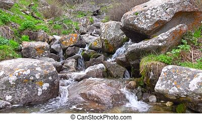 Small mountainous waterfall among lichen covered rocks 4K...