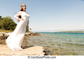 Fairy at the ocean - A young beautiful woman standing at the...