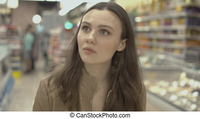 Sweet young woman walking on the supermarket and places meat...