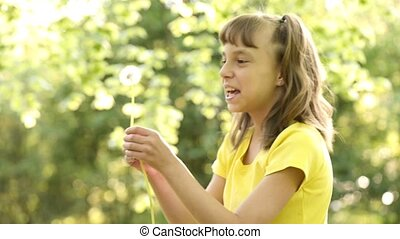 Happy little girl blowing a dandelion off making a wish....