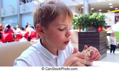 the child eats a chicken in a fast food