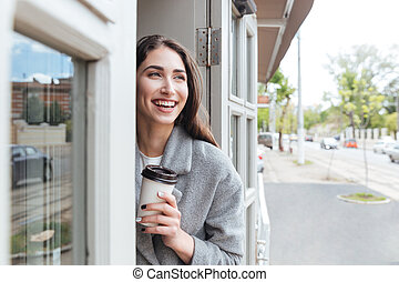 Happy cheerful smiling girl holding take away coffee at the...