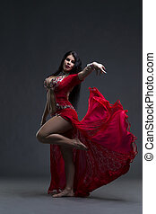 Young beautiful exotic eastern women performs belly dance in ethnic red dress on gray background