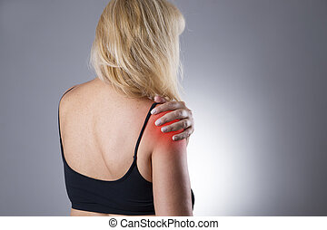 Woman with pain in shoulder Pain in the human body on a gray...