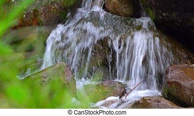 Small mountainous waterfall among lichen covered rocks. 4K close up shot