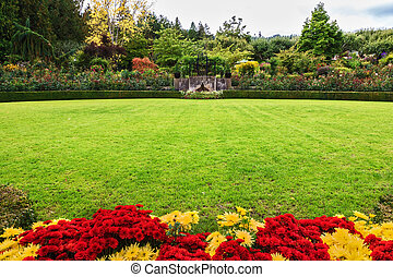 Green grass lawn and flower beds - Picturesque ornamental...