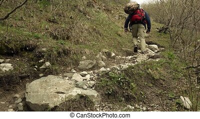 Hiker with red backpack walking uphill 4K video - Hiker with...