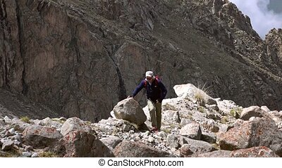 Hiker in sunglasses with red backpack walking uphill 4K...