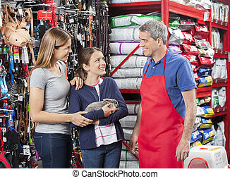 Happy Mother And Daughter Buying Rabbit From Salesman -...