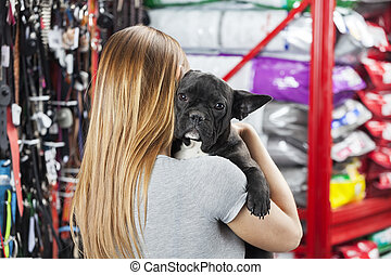 Woman Carrying French Bulldog At Pet Store - Rear view of...