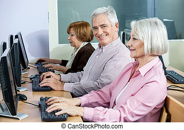Happy Senior Man Sitting At Desk In Computer Class -...