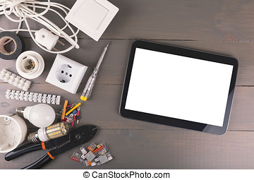 blank digital tablet with electrical tools and accessories on wooden table