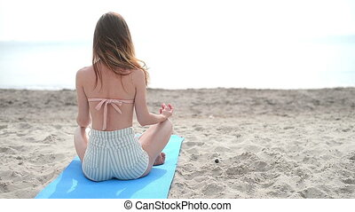 Portrait of young woman practicing yoga in summer...