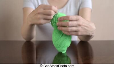 Woman clewing the green yarn up on a wooden table