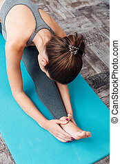 Young fitness woman doing splits isolated on grey background