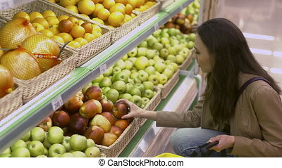 Beautiful young woman picks apples and lemons in the...
