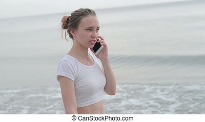 young woman with mobile phone on a beach - young woman with...