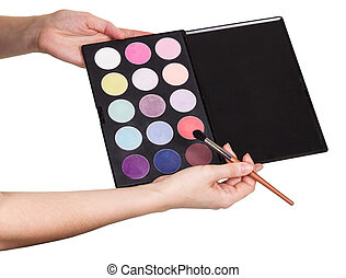 Female hands eyeshadow palette and cosmetic brush isolated...
