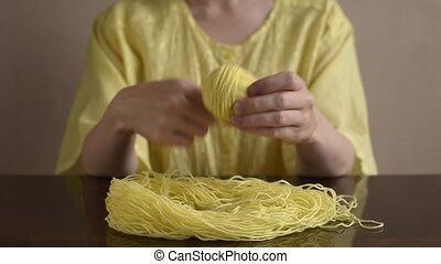 Woman clewing up the yellow yarn up on a wooden table.
