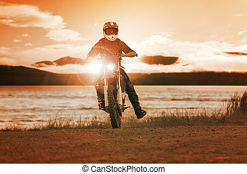 man riding enduro motorcycle in motor cross track use for...