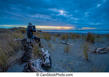 tourist man taking a photography at hokitika beach south...