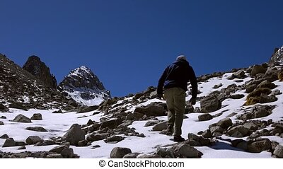 Lone hiker clmbs uphill on snow covered rock 4K video - Lone...