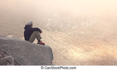 Young man sitting on rock and sightseeing beautiful hazy mountains. 4k shot