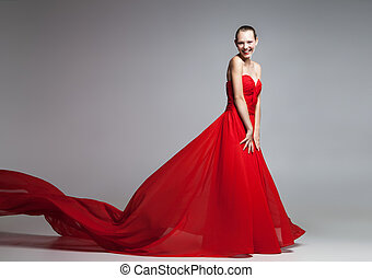 Beautiful young girl in red dress with flying skirt looking...
