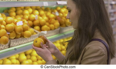 Cute girl chooses fresh citrus fruits in the supermarket and...