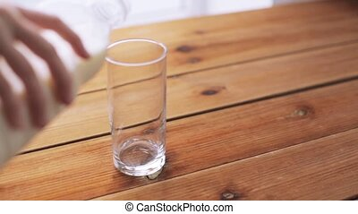 hand pouring milk into empty glass on wooden table - healthy...